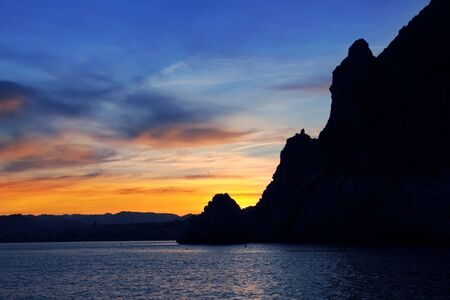 Cape San Antonio Javea Xabia sunset view from sea Mediterranean backlight Alicante Spain photo