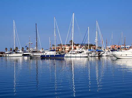 Boats in blue marina Mediterranean sea Denia ship poles reflection Stock Photo - 9494450