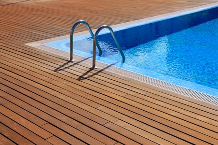 pool deck: blue swimming pool with teak wood flooring stripes summer vacation