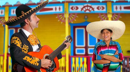 Mexican mariachi charro man and poncho Mexico girl colorful facade houses photo