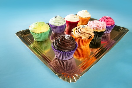 Cupcakes colorful cream muffin arrangement in golden mirror tray photo