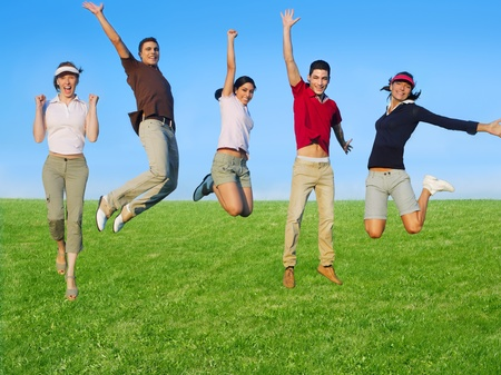 Jumping young people happy group in meadow blue sky outdoor Stock fotó