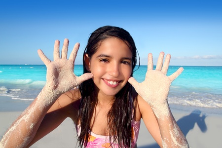 latin indian teen girl playing beach showing sandy hands in Caribbean tropical sea photo