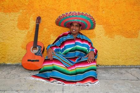 trajes mexicanos: Feliz mexicano sentarse guitarra de hombre sombrero t�pico sombrero colorido serape  Foto de archivo