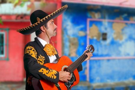 mariachi: Charro Mariachi zanger spelen gitaar in Mexico huizen achtergrond Stockfoto