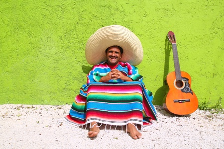 poncho: Mexican typical lazy topic man guitar poncho sit in green wall Stock Photo