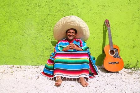 trajes mexicanos: Mexicano tema perezoso t�pico hombre guitarra poncho sit en pared verde