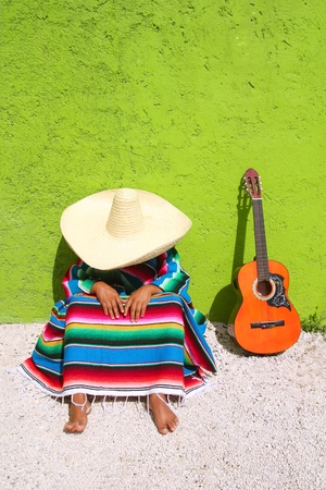 Nap lazy typical mexican sombrero man sitting on green wall  Stock Photo - 9607644
