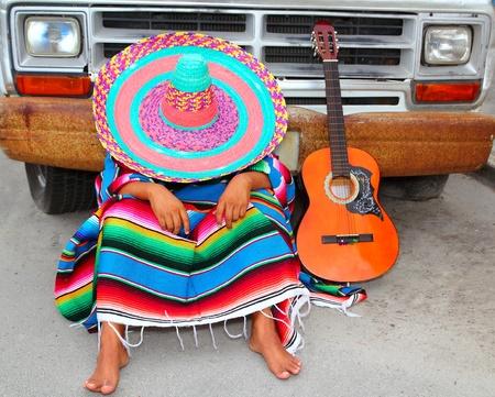trajes mexicanos: Chico mexicano pan perezoso, durmiendo en coche grunge con guitarra y poncho Foto de archivo