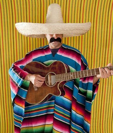 Mexican man serape poncho sombrero playing guitar typical Mexico photo