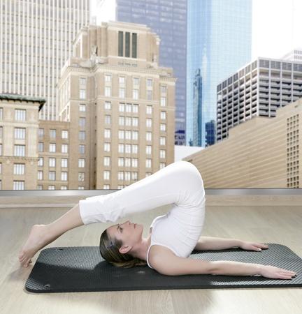 saxy: black mat yoga woman window view of city urban buildings Stock Photo