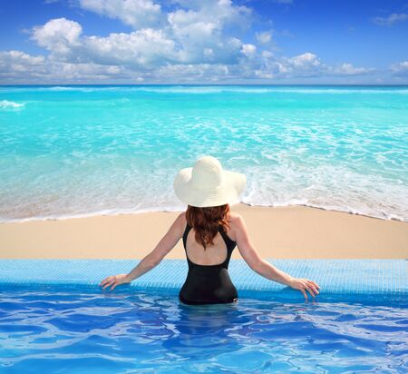 Caribbean tropical sea view from blue pool rear woman beach hat photo