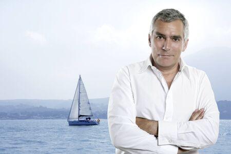 beach senior tourist summer vacation white shirt mediterranean sailboat mountain coast