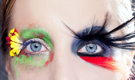 asymmetrical fantasy eyes makeup spring flowers and night black bird feathers photo
