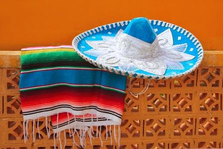 traje mexicano: poncho charro mariachi sombrero mexicano azul serape sobre muro de azulejos naranja