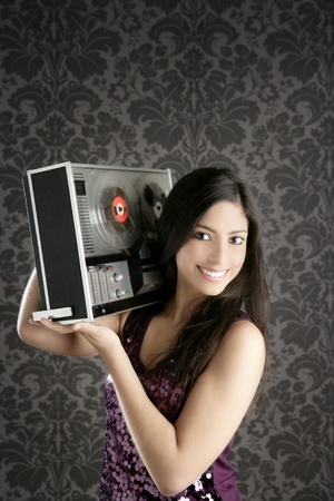 tape recorder:  Retro open reel tape recorder beautiful brunette Dj hearing music gray walpaper Stock Photo
