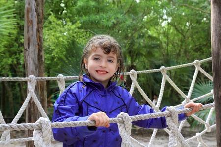 adventure brunette happy little girl on jungle park rope bridge photo