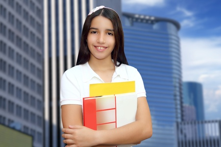 Brunette student young girl teen latin holding books modern city buildings photo