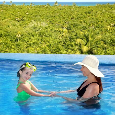 daughter and mother in swimming pool tropical location background photo