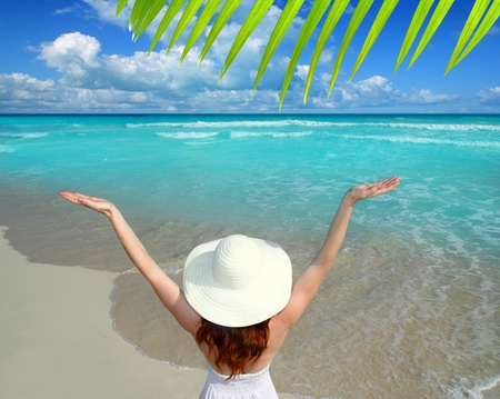 Caribbean beach woman rear view hat open arms happy vacation gesture photo