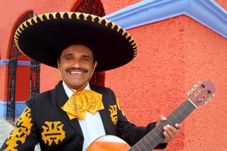 mariachi: Charro Mariachi zanger met gitaar spelen in Mexico huizen achtergrond