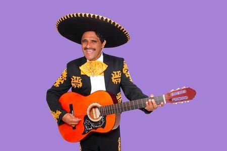 traje mexicano: Charro Mariachi cantar tocando la guitarra en fondo púrpura Foto de archivo
