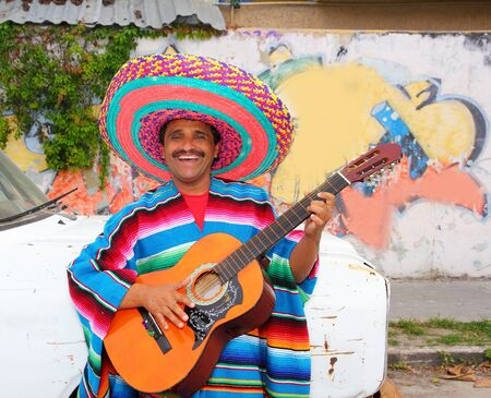 Mexican humor man smiling playing guitar sombrero poncho in street photo