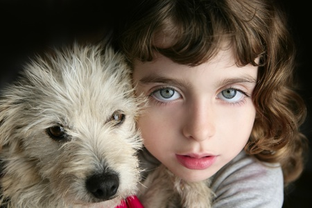hairy closeup: dog puppy and girl hug portrait closeup blue eyes white hairy little doggy Stock Photo