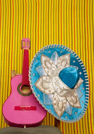 mexico culture: mariachi embroided sombrero and pink guitar in striped mexican background