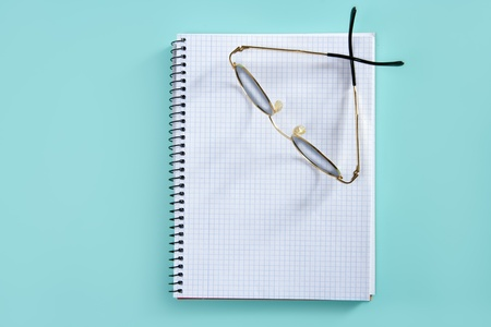 doctor or teacher glasses on blank spiral notebook copyspace over green photo