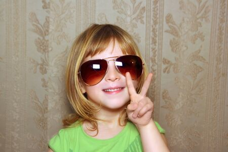 little girl with hand victory gesture and funny sunglasses retro wallpaper Stock Photo - 9941589