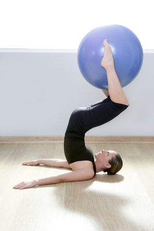 pilates instructor woman with stability ball doing gym fitness yoga exercises photo