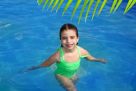 brunette little girl in swimming pool smiling with missing front teeth photo