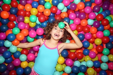 playcentre: little smiling girl playing lying in colorful balls park playground