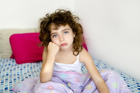 bedcover: brunette girl bored in her bedroom bed with messy hair