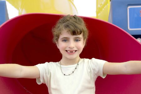 blue eyes indented girl smiling in red playground photo