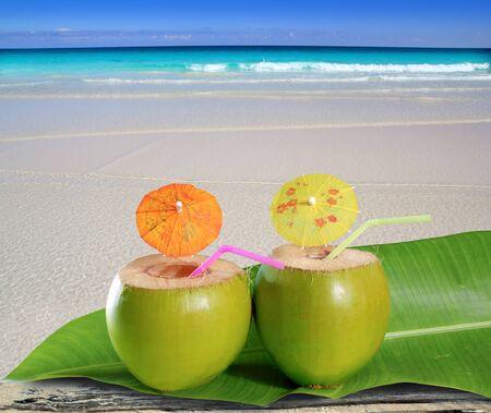 coco: cocteles frescos Cocos verdes tiernos paja en una playa del Caribe tropical