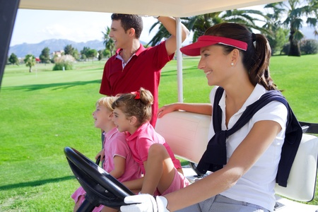 golfing: golf course family father mother and daughters on buggy in a green grass field Stock Photo