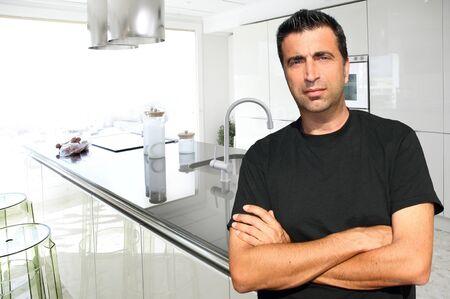 Medium age man in modern kitchen inter portrait crossed arms Stock Photo - 9941818
