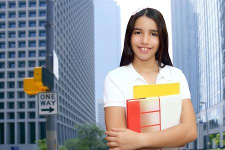 brunette teen  indian latin student holding school books in modern city buildings photo