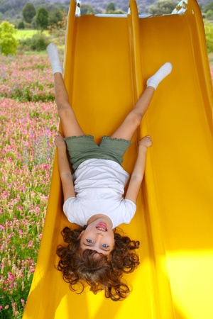 cabeza abajo: upside down little girl on playground slide laughing in pink flower meadow