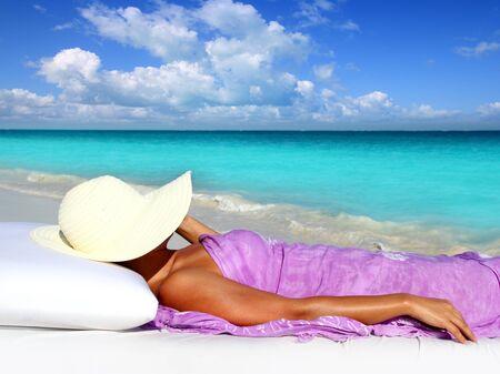 sunbath: Caribbean toeristische rusten in tropisch strand met hoed liggend op resort bed
