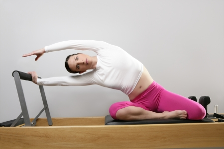gym woman pilates instructor stretching in reformer bed Stock Photo - 9941760