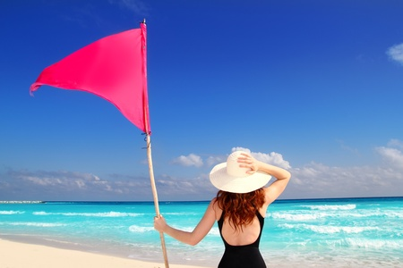 girl with swimming suit holding red beach flag pole rear view in Caribbean sea photo
