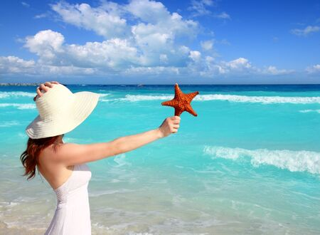 mayan riviera: beach hat woman holding starfish with hand in a tropical turquoise sea