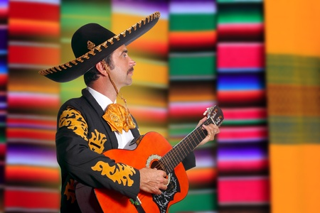 Charro Mariachi profile man playing guitar with blurred serape background photo