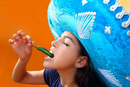 Mexican girl profile eating jalapeno hot chili pepper with blue mexican hat photo