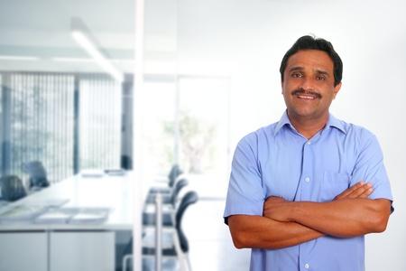 indianin: Indian latin biznesmen z niebieskÄ… bluzkÄ™ w nowoczesnym biurze tle Zdjęcie Seryjne