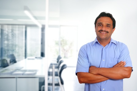 casual meeting: Indian latin businessman with blue shirt in modern office background