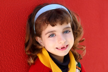 front teeth indented little girl smiling on a red wall background photo